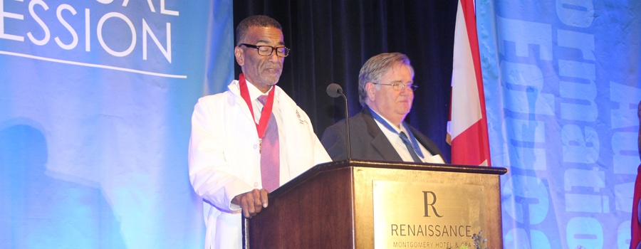 two men standing at podium; one in white physician's coat