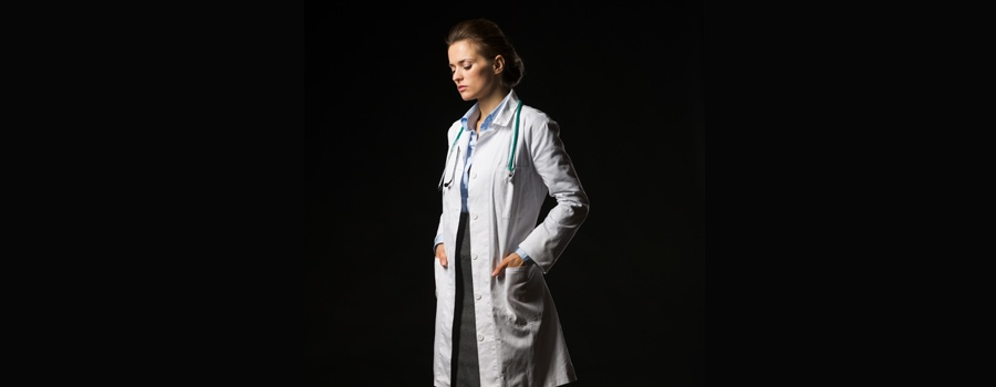 Female physician standing in darkness