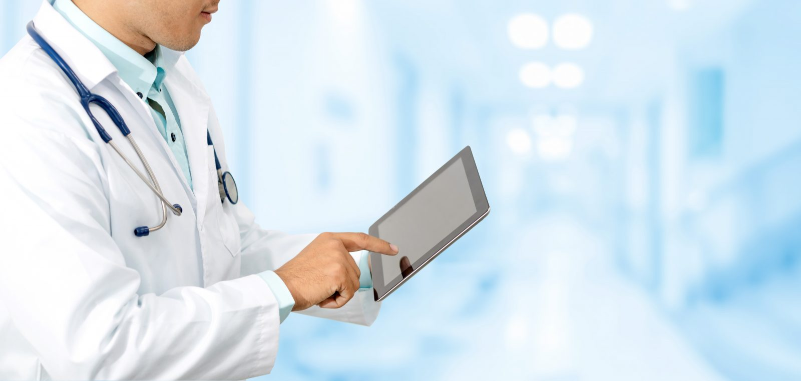 Doctor with tablet computer at hospital.